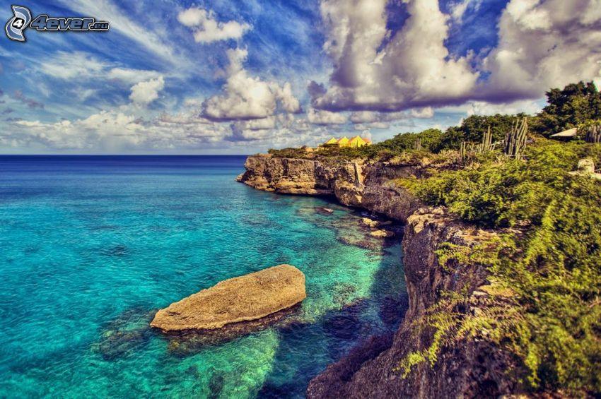 klippor vid kusten, grunt azurblå hav, moln