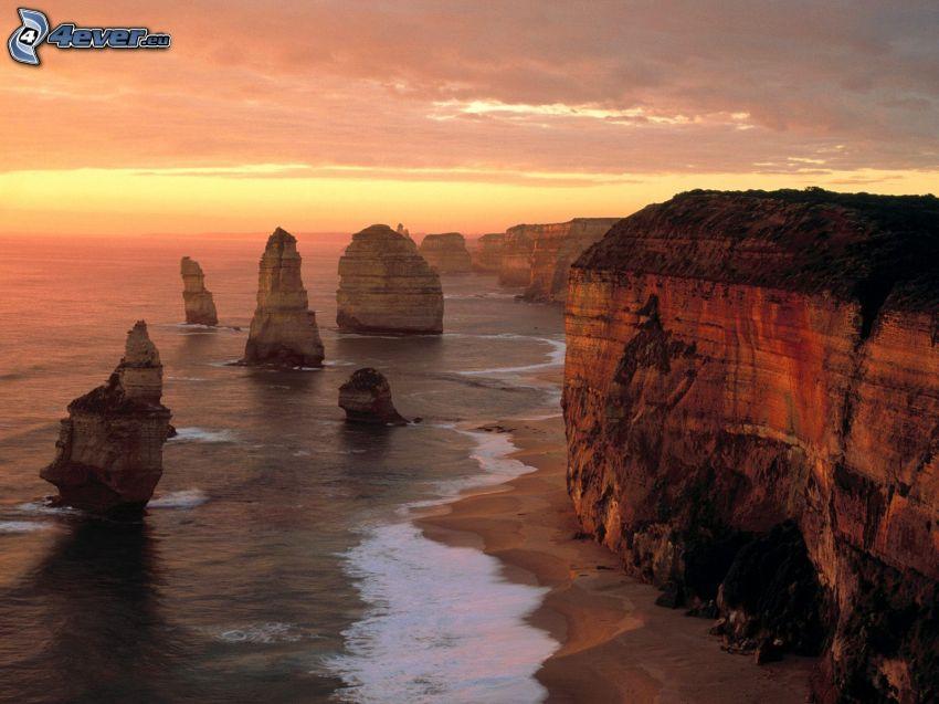 klippor vid kusten, kvällshimmel