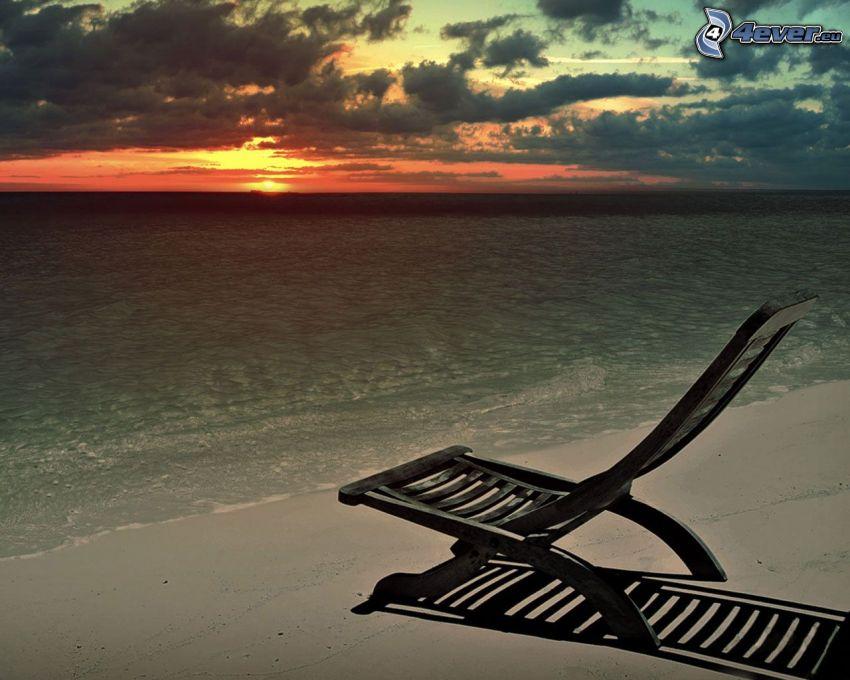 mörk solnedgång, solstolar på stranden, sandstrand, hav