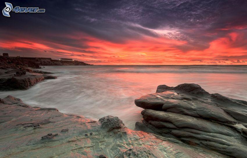 öppet hav, orange himmel, stenig kust