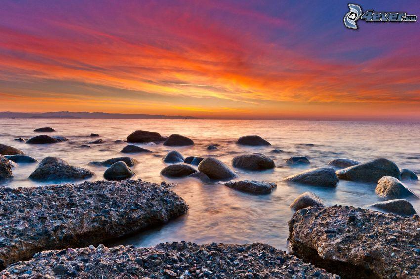 orange solnedgång, strand efter solnedgång, stenig strand
