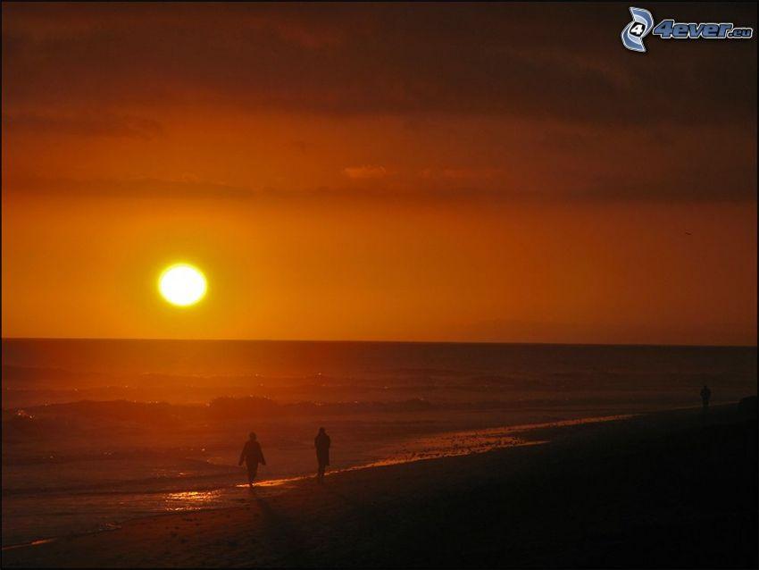 orange solnedgång över havet, silhuetter av människor, kvällsstrand