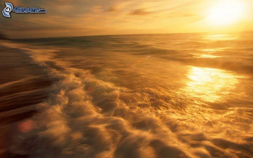 orange solnedgång över havet, vågor