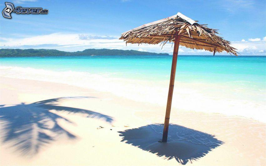 parasoll på stranden, azurblå hav, sandstrand