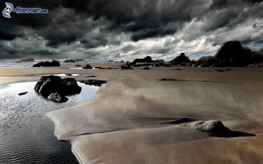 sandstrand, klippor, mörka moln