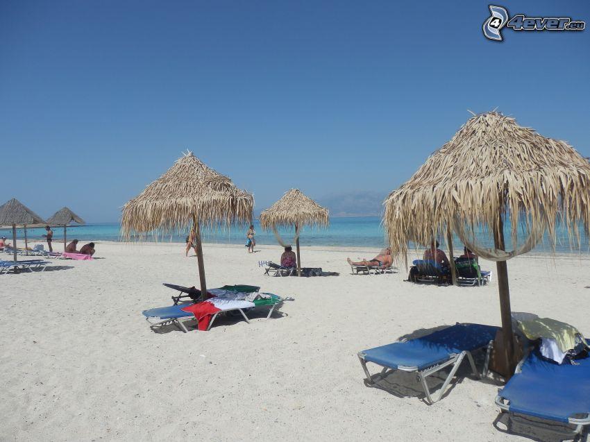 sandstrand, parasoller på strand, solstolar, människor