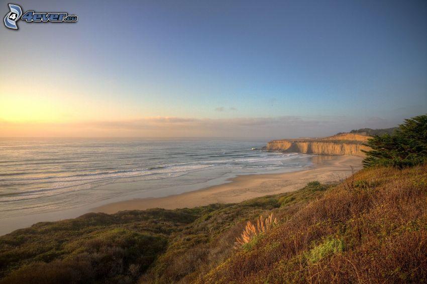 sandstrand, solnedgång över havet, klippor vid kusten