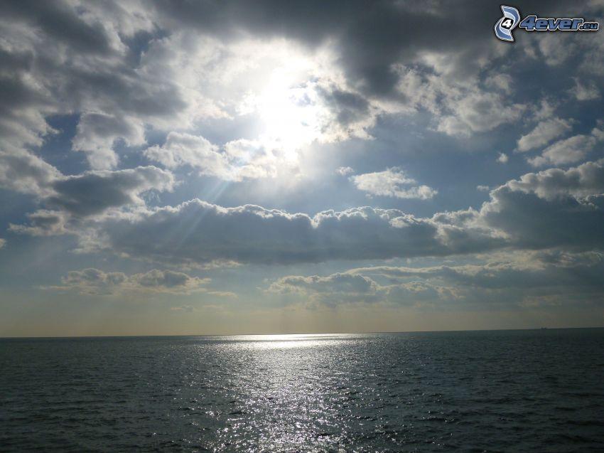 sol bakom molnen, hav