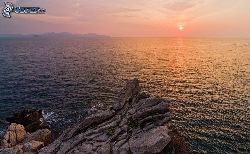 solnedgång över hav, klippor i havet