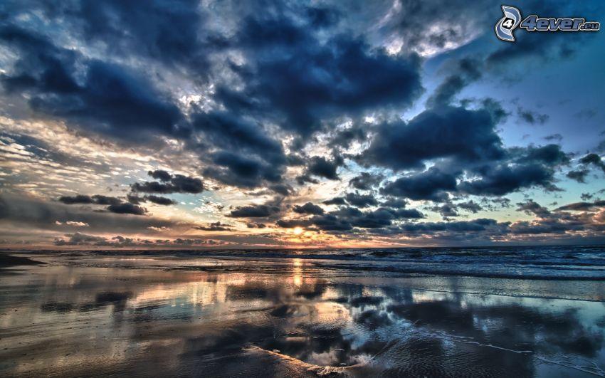 solnedgång över hav, moln, sandstrand, öppet hav