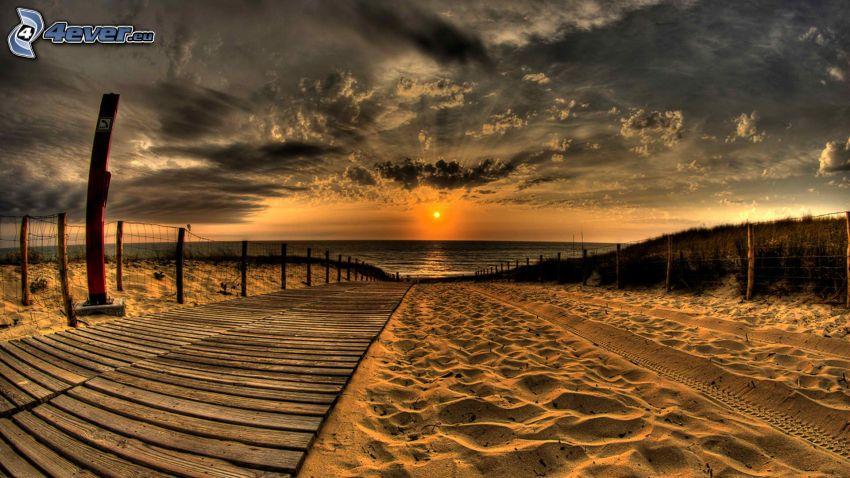 solnedgång över hav, mörk himmel, sandstrand, trottoar, HDR
