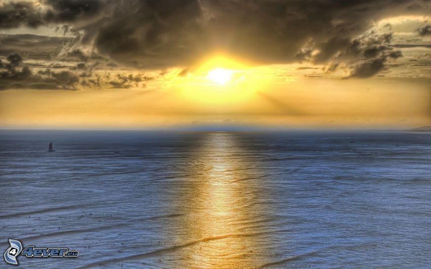solnedgång över hav, mörk himmel
