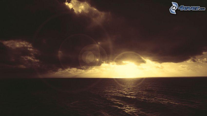 solnedgång över hav, mörka moln