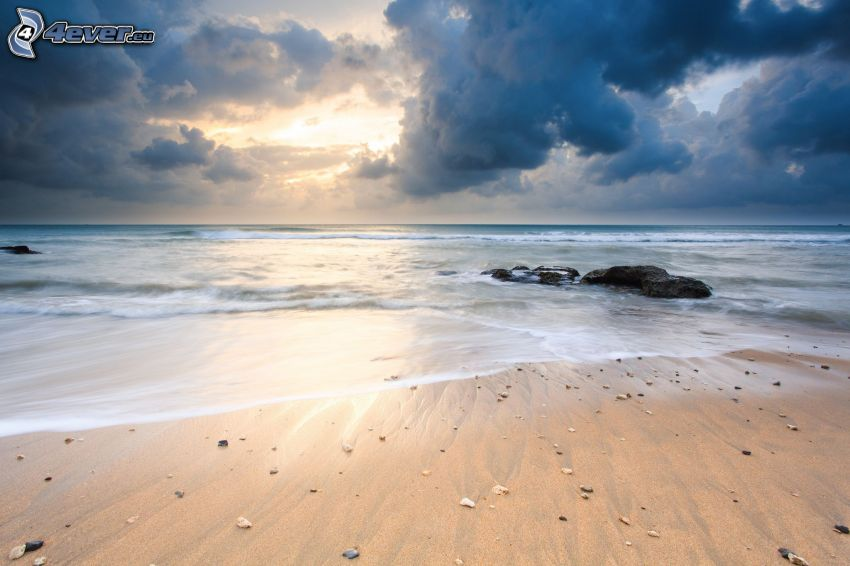 solnedgång över hav, sandstrand, mörka moln