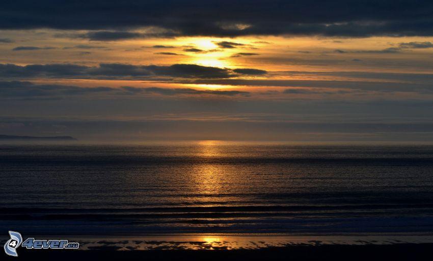 solnedgång över hav, solnedgång i moln, kvällsstrand
