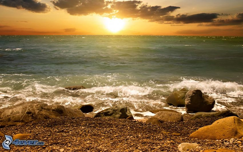 solnedgång över hav, stenig kust