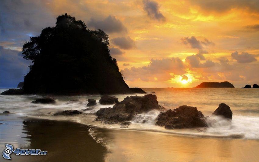 solnedgång över havet, klippö, sandstrand, stenar