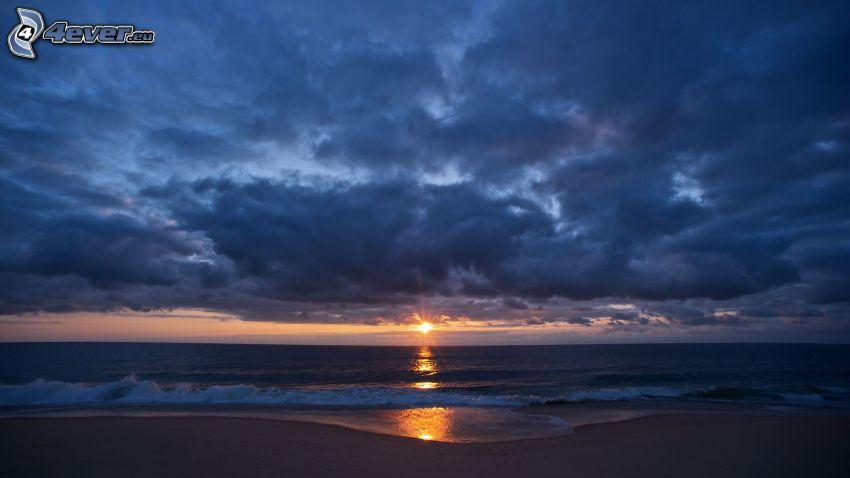 solnedgång över havet, mörk himmel, sandstrand