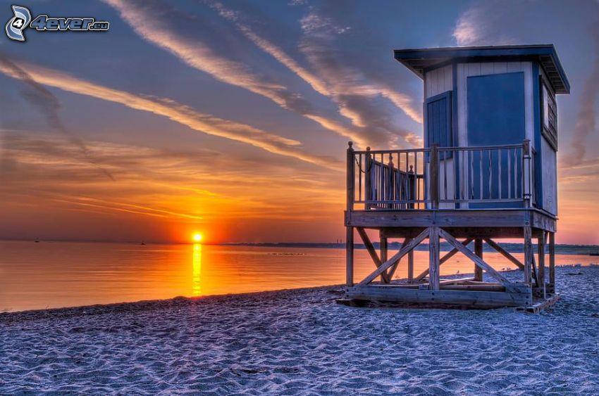 solnedgång över havet, sandstrand, hus