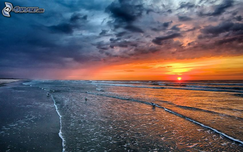 solnedgång över havet, sandstrand, mörka moln