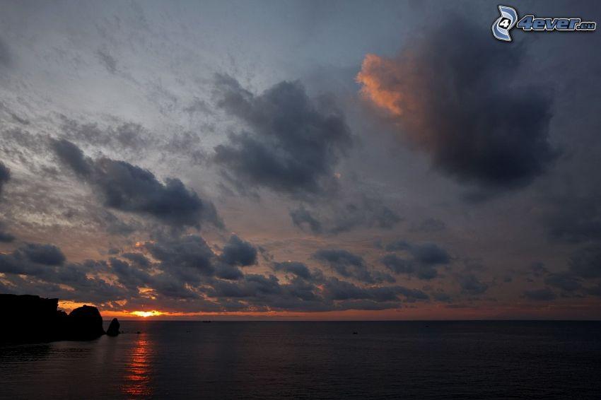 solnedgång över havet, sol bakom molnen