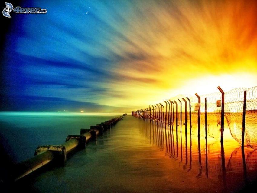 solnedgång över havet, staket, öppet hav