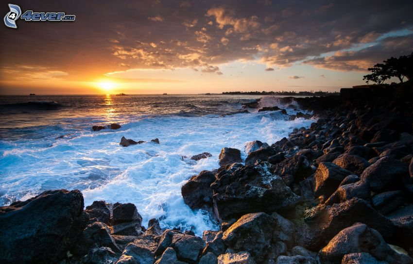 solnedgång över havet, stenig kust