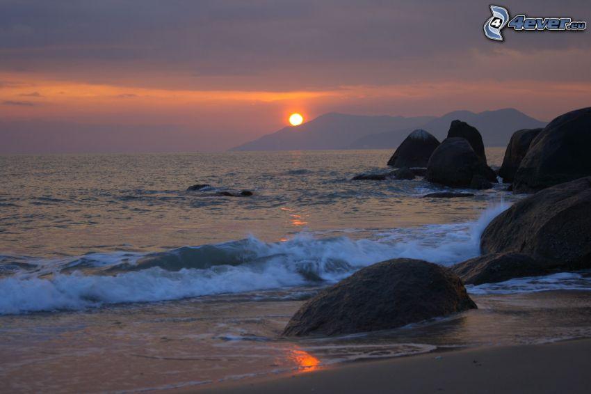 solnedgång över kulle, klippor i havet, stenbumlingar