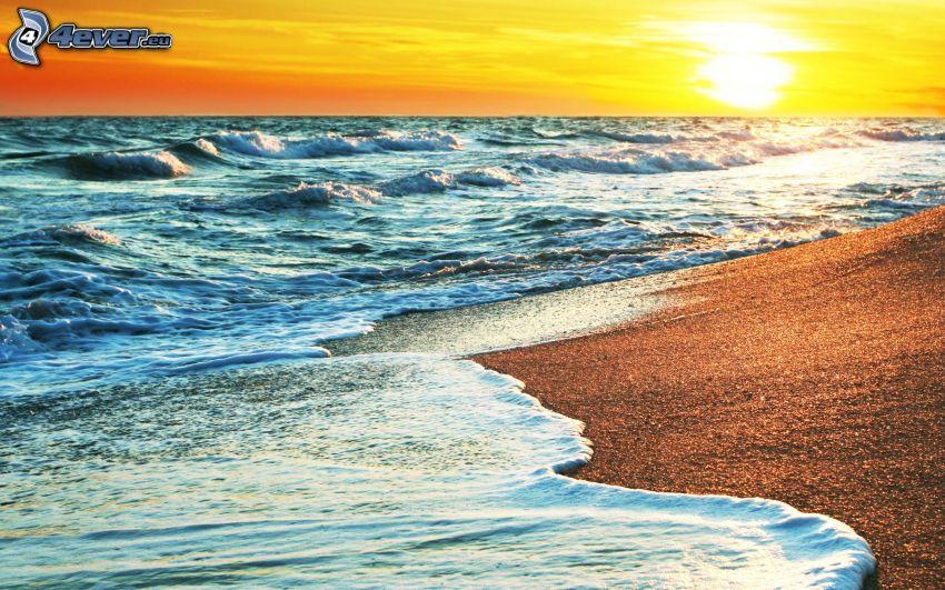 solnedgång över strand, hav, vågor vid kusten, gul himmel