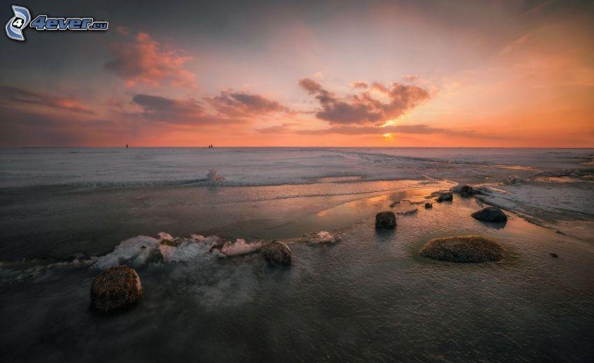 solnedgång vid havet, orange himmel, stenar