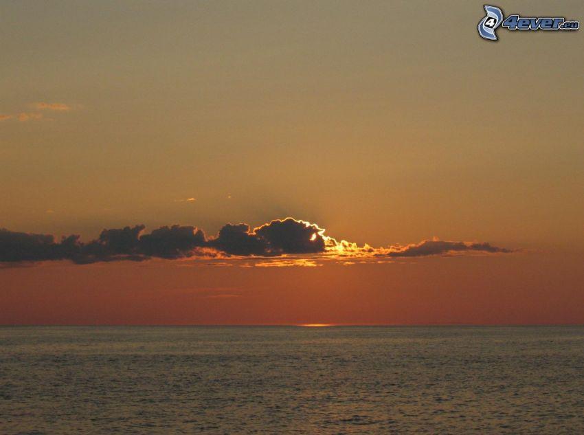 solnedgång vid havet, sol bakom molnen
