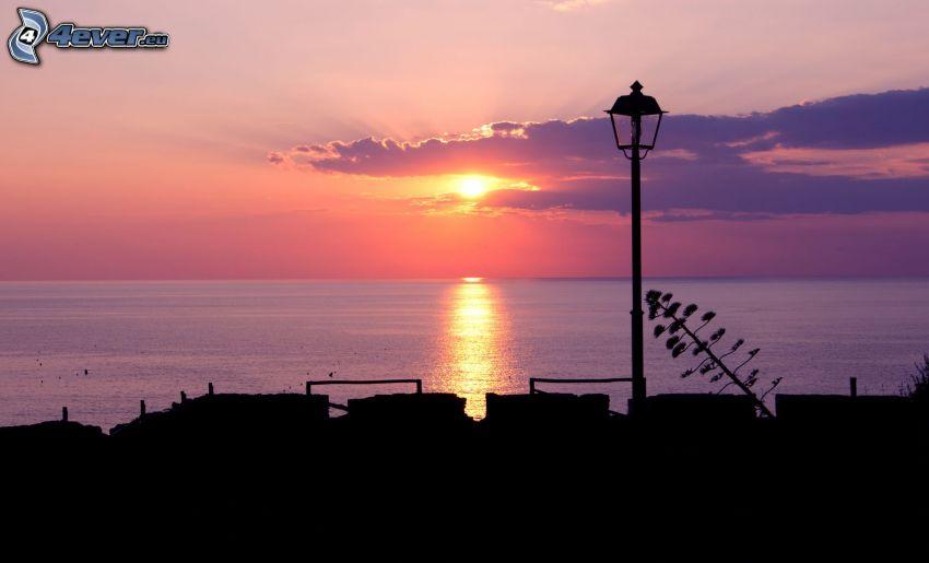 solnedgång vid havet, solnedgång i moln, lila himmel, gatlykta, siluetter