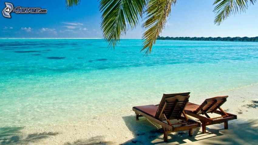 solstolar på stranden, azurblå sommarhav