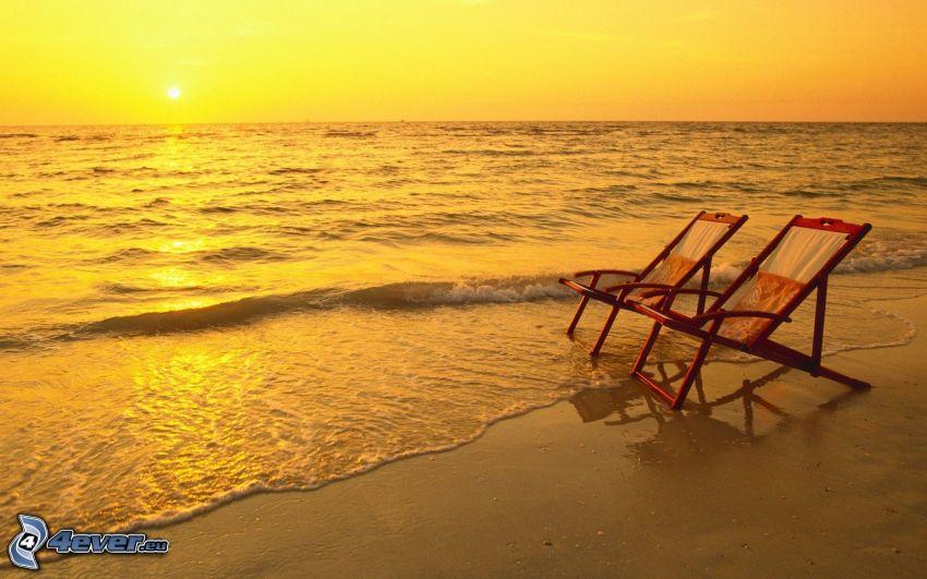 solstolar på stranden, solnedgång över hav