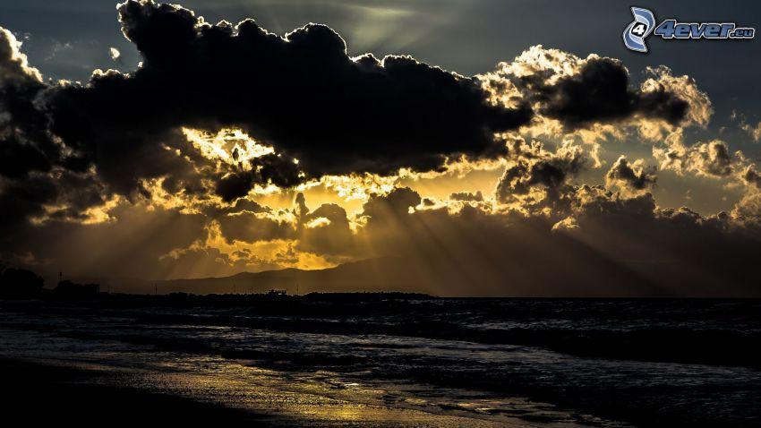 solstrålar bakom moln, hav
