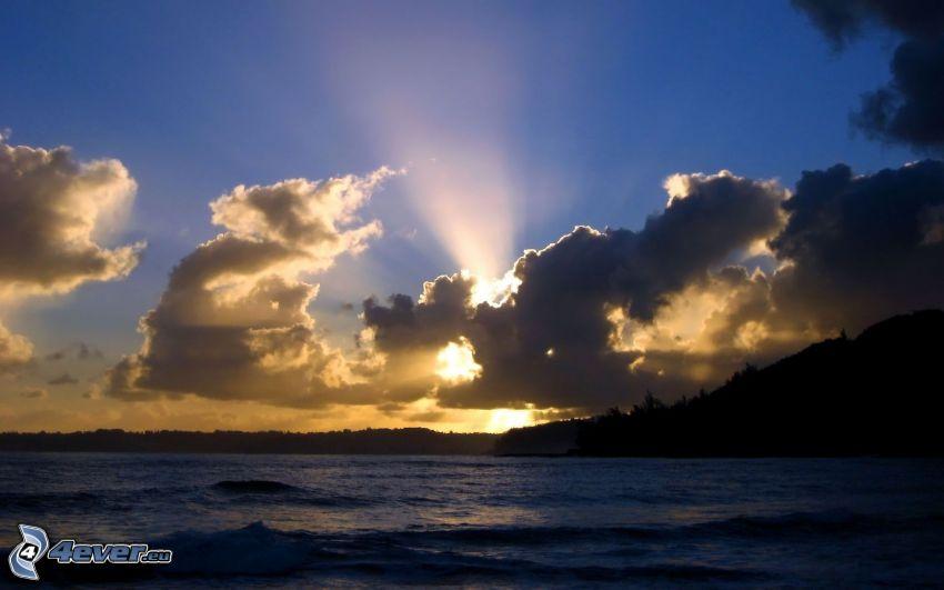 solstrålar bakom moln, solnedgång i moln, hav