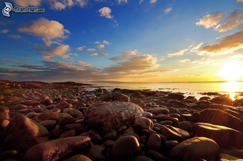 stenig kust, solnedgång över hav