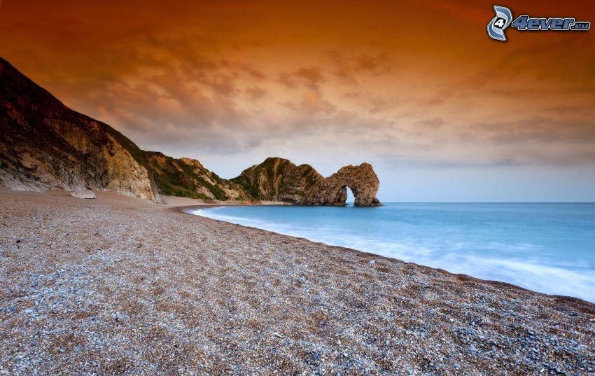 stenig strand, port av klippor i havet, orange himmel