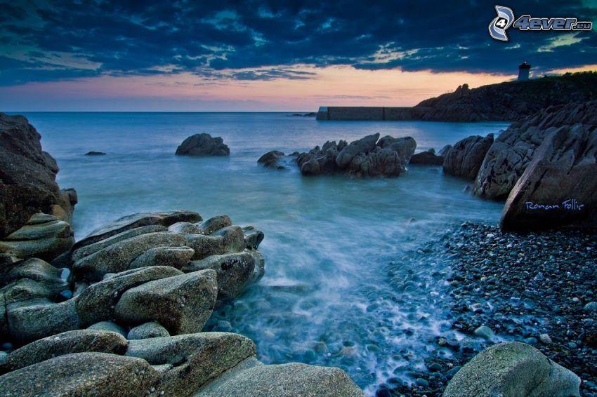 stenig strand, vik, klippor i havet, kvällshimmel