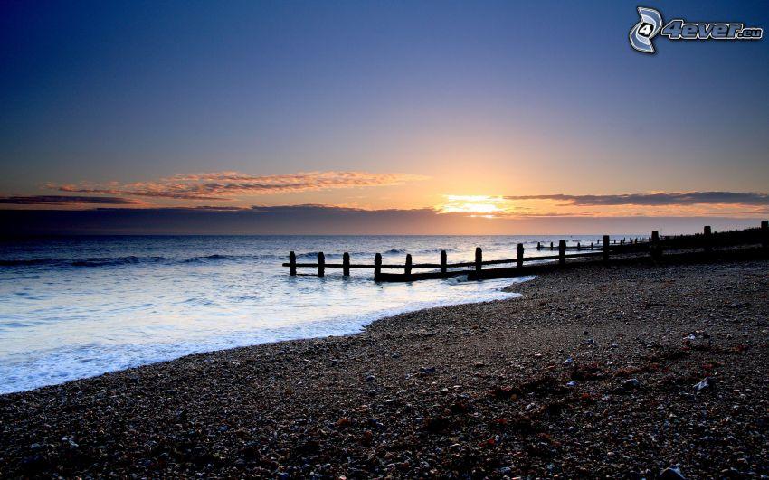 strand i solnedgång, stenig strand, brygga
