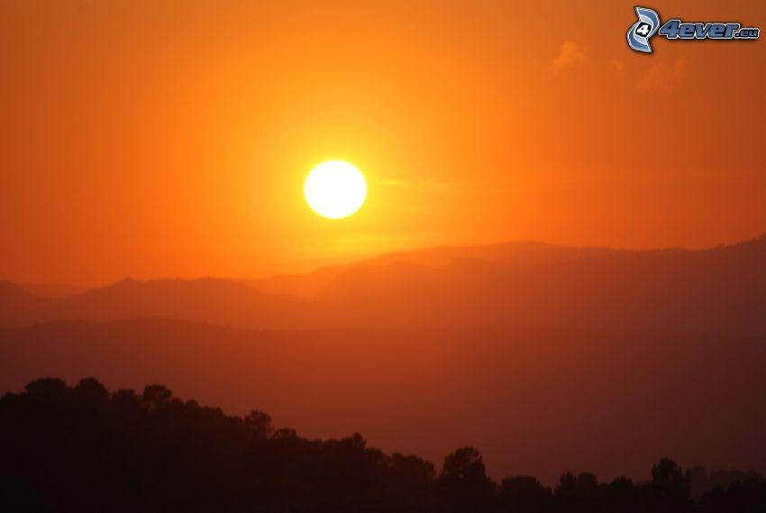 orange solnedgång, kullar