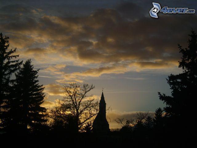 silhuett av kyrka, siluetter av träd, moln