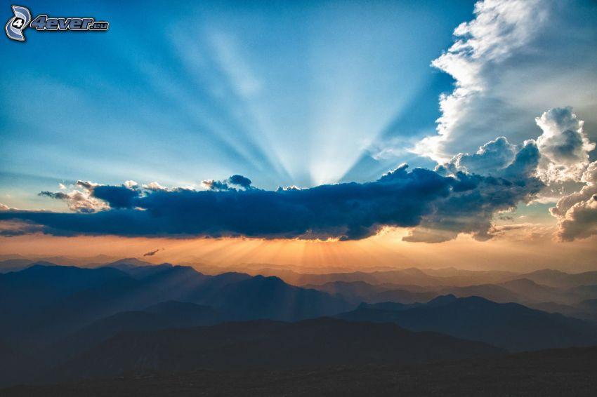 sol bakom molnen, solstrålar, berg