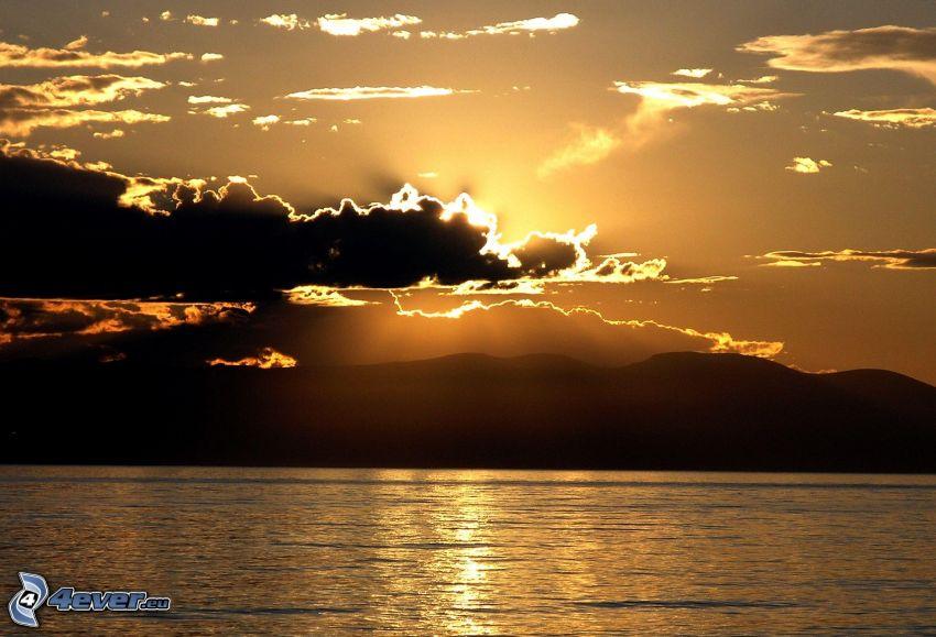 solnedgång över sjö, sol bakom molnen