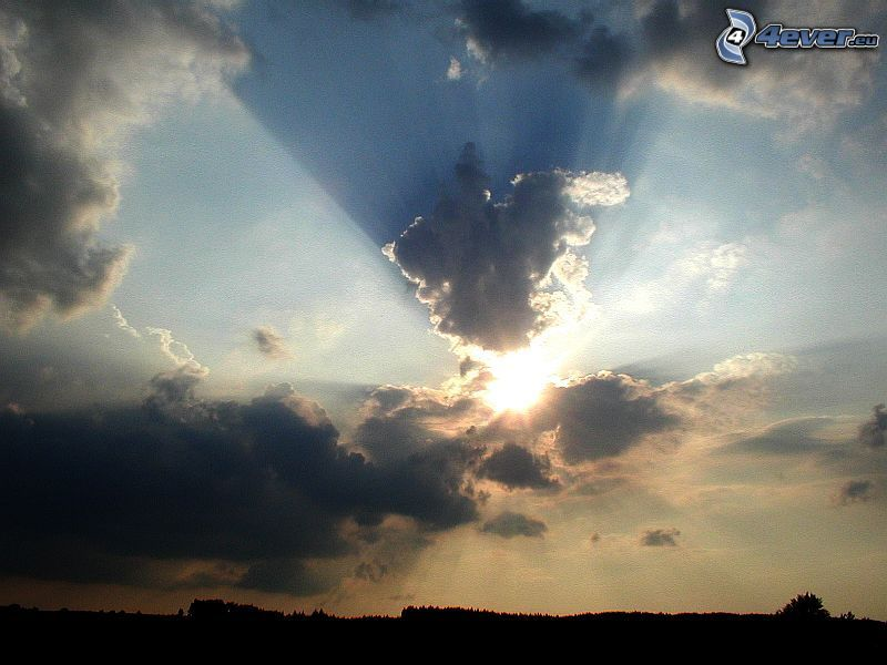 solstrålar bakom moln, silhuett av horisont