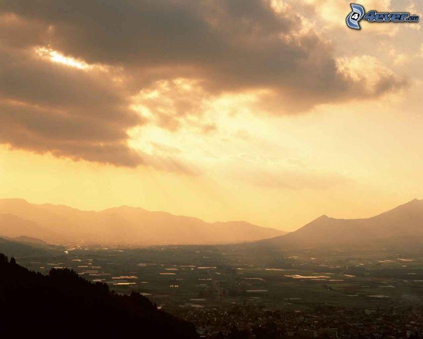 utsikt över landskap, solstrålar, berg, mörka moln