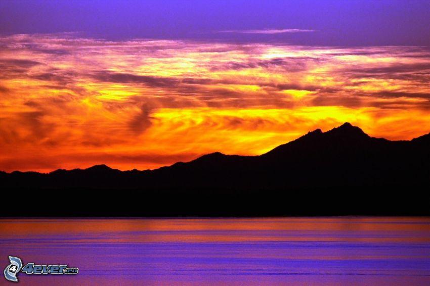 orange solnedgång, bergskedja, orangea moln, stor sjö