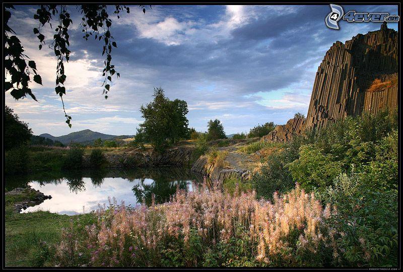 sjö, klippigt berg, lugn vattenyta, blommor, träd vid sjö