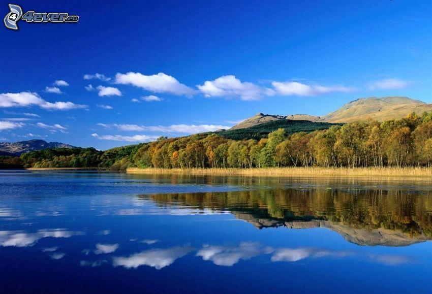 sjö, kullar, höstträd, spegling
