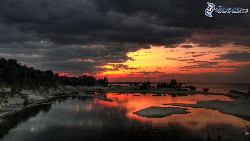 skog efter solnedgången, röd himmel, sjö, grusdamm, moln
